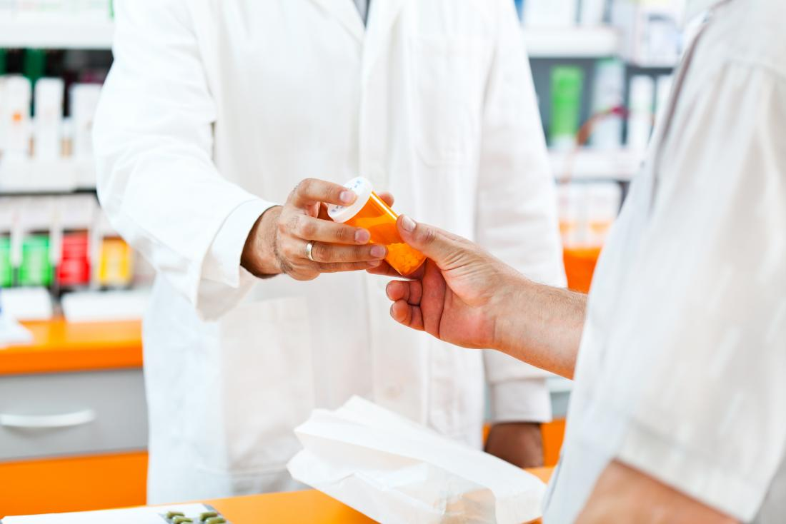 Pharmacist handing over tablets to man