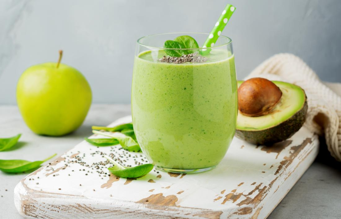 Green smoothie with apple and avocado on chopping board
