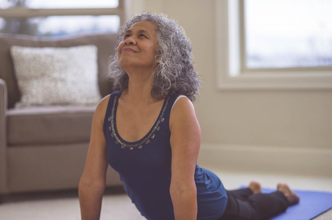 Elderly woman lifts her torso off the floor in a yoga pose at home