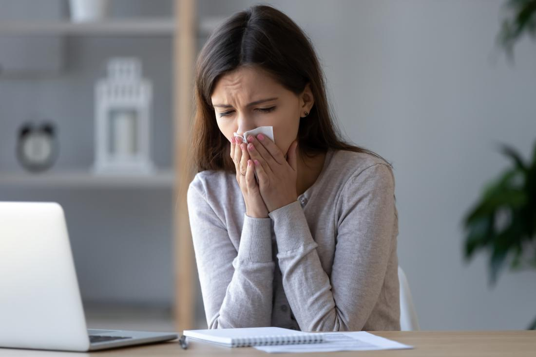 Woman coughing into a tissue due to a lower respiratory tract infection