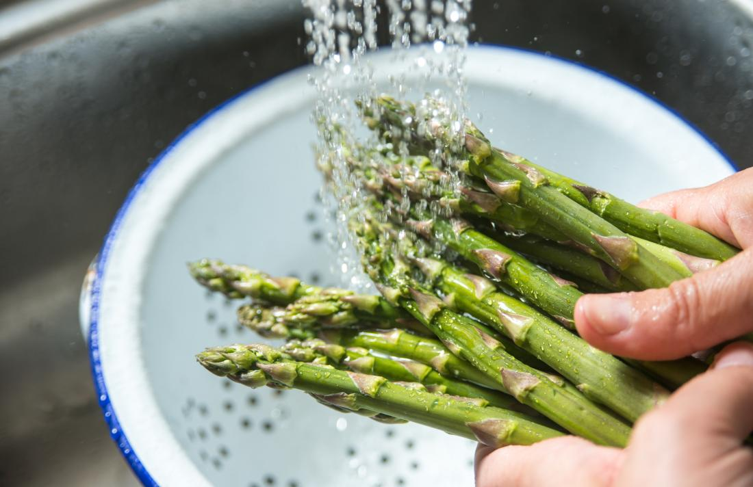 Asparagus being washed under a tap
