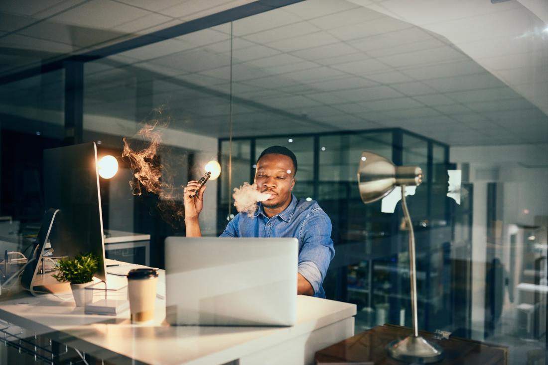man vaping at his desk