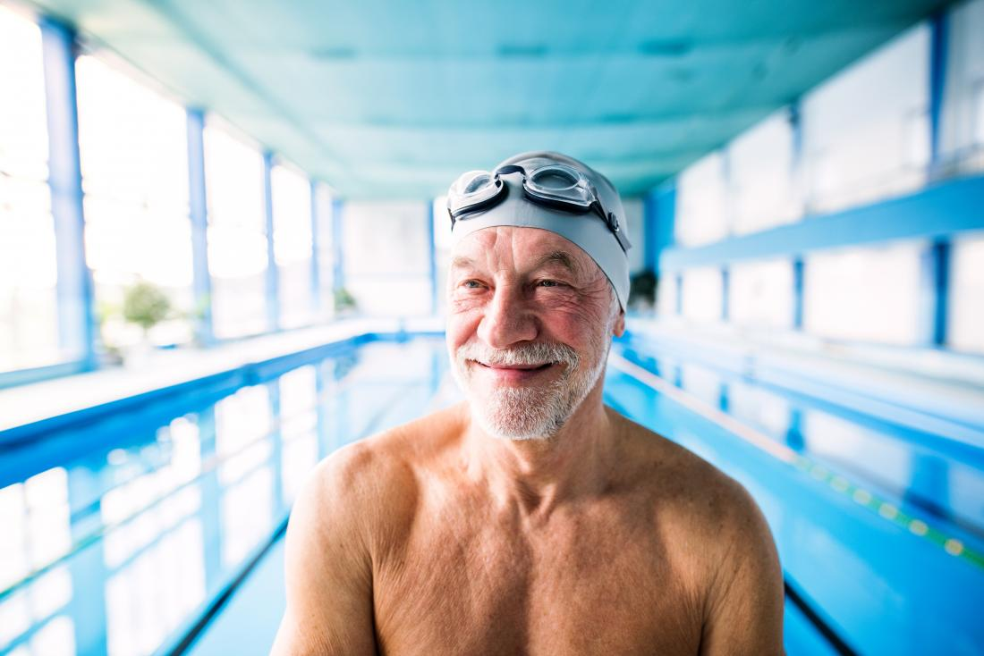 Senior man in swimming pool with goggles for aquatic exercises, as home remedy for arthritis pain relief