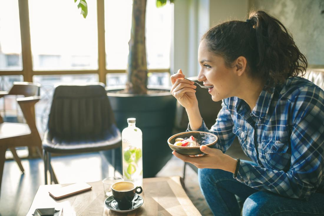 young woman eating fruit and yoghurt