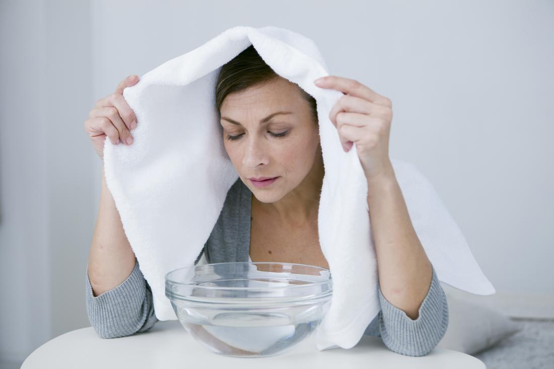 Woman with head over steaming bowl of water to clear sinuses