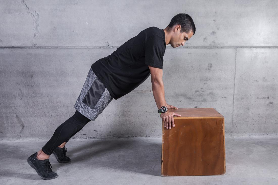 Person performing incline pushup against wooden block.