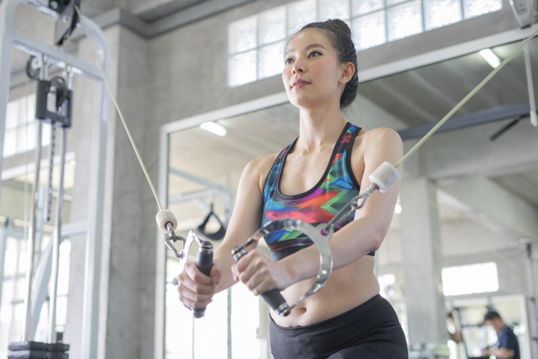 Woman performing cable crossover exercise in gym
