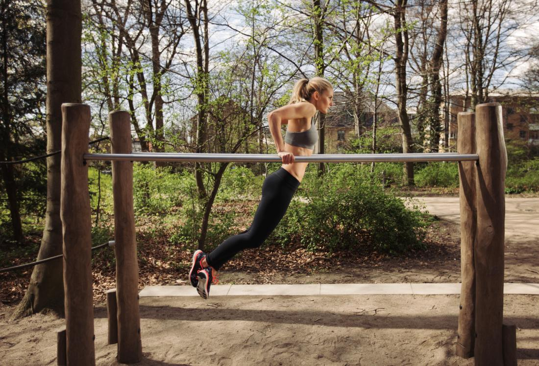 Woman performing parallel bar dips in exercise park