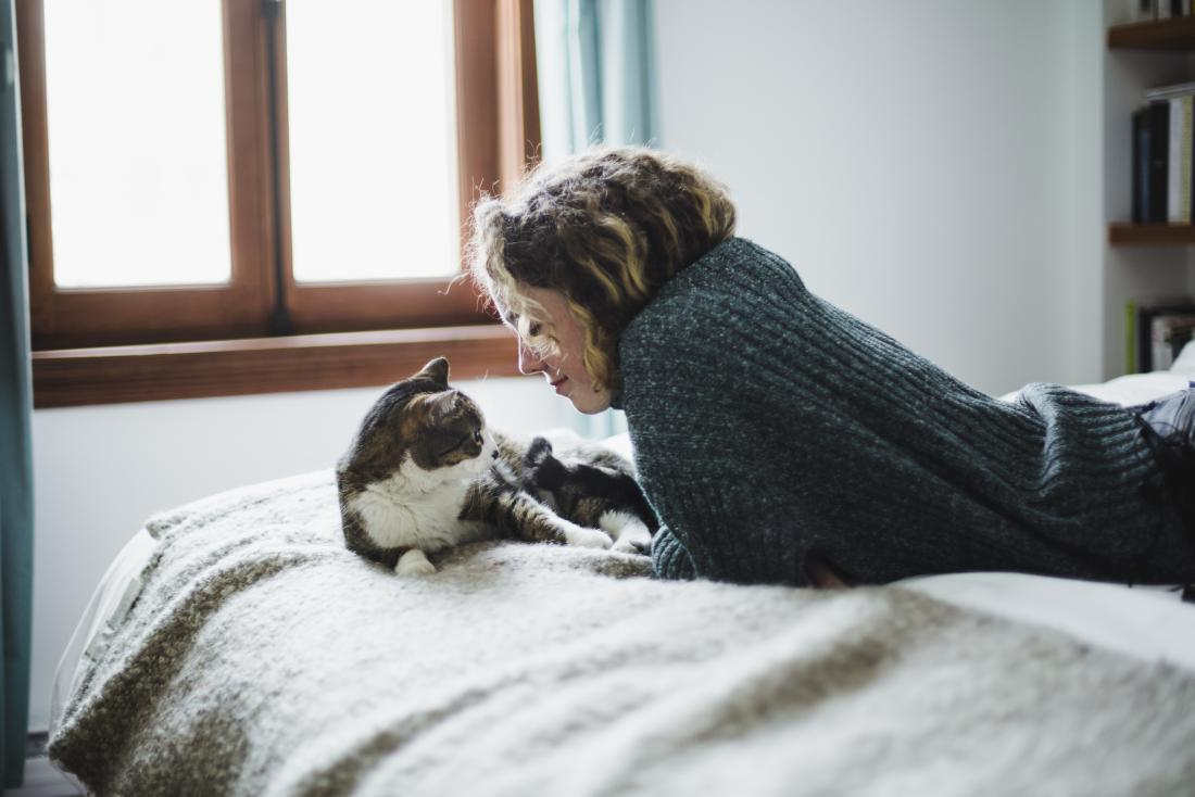 Woman playing with her cat to distract from other issues