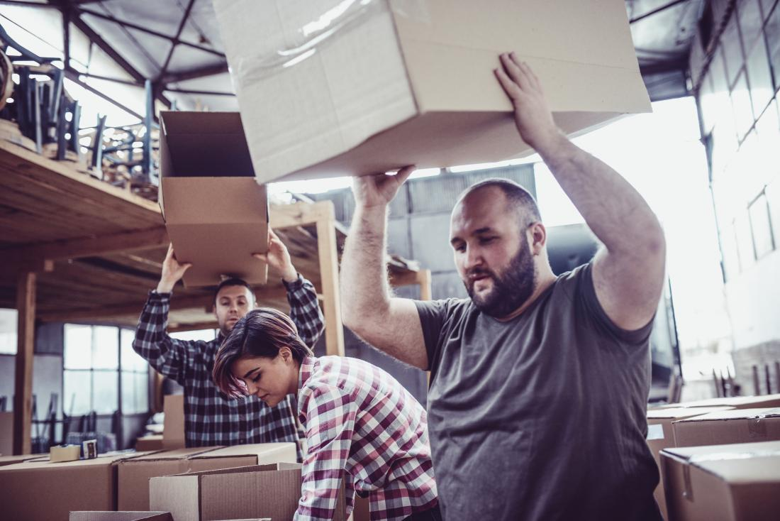 People in a warehouse lifting boxes