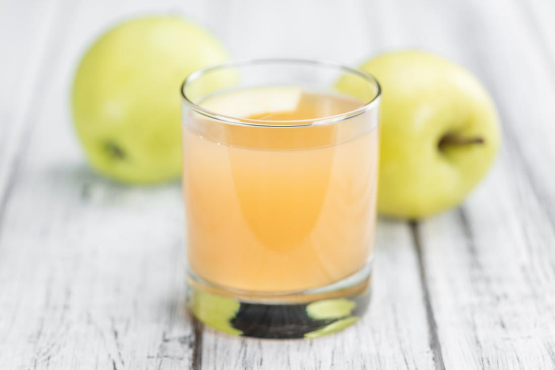 Cloudy apple juice on wooden table with whole green apples in background