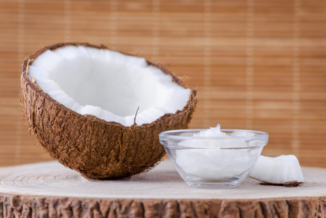 half a coconut and coconut oil in a bowl