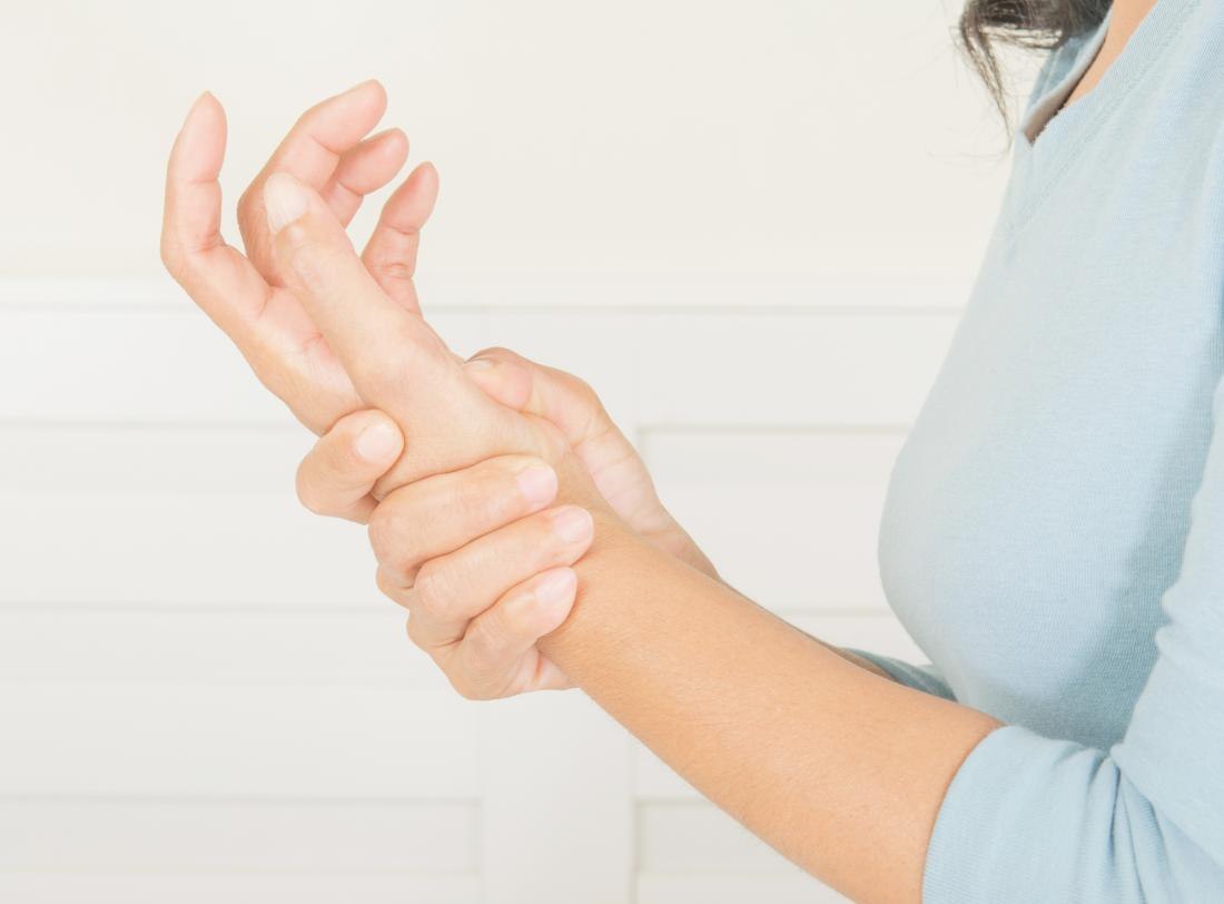 Woman holding her hand in pain
