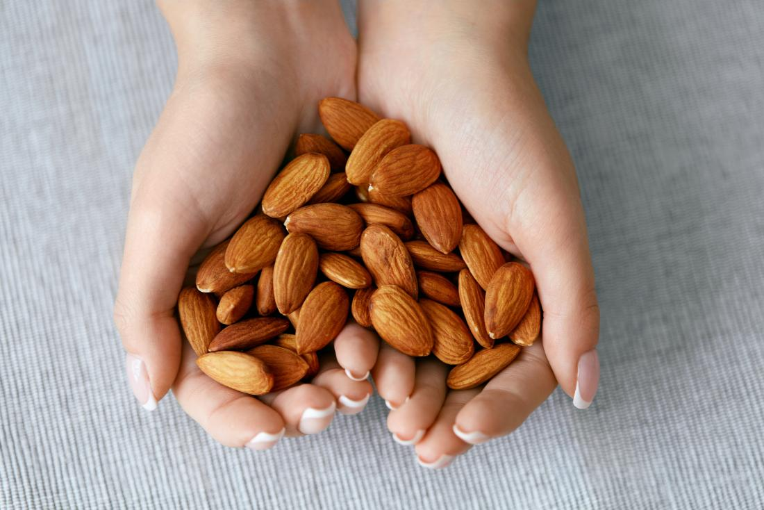 close up of womans hand holding almonds