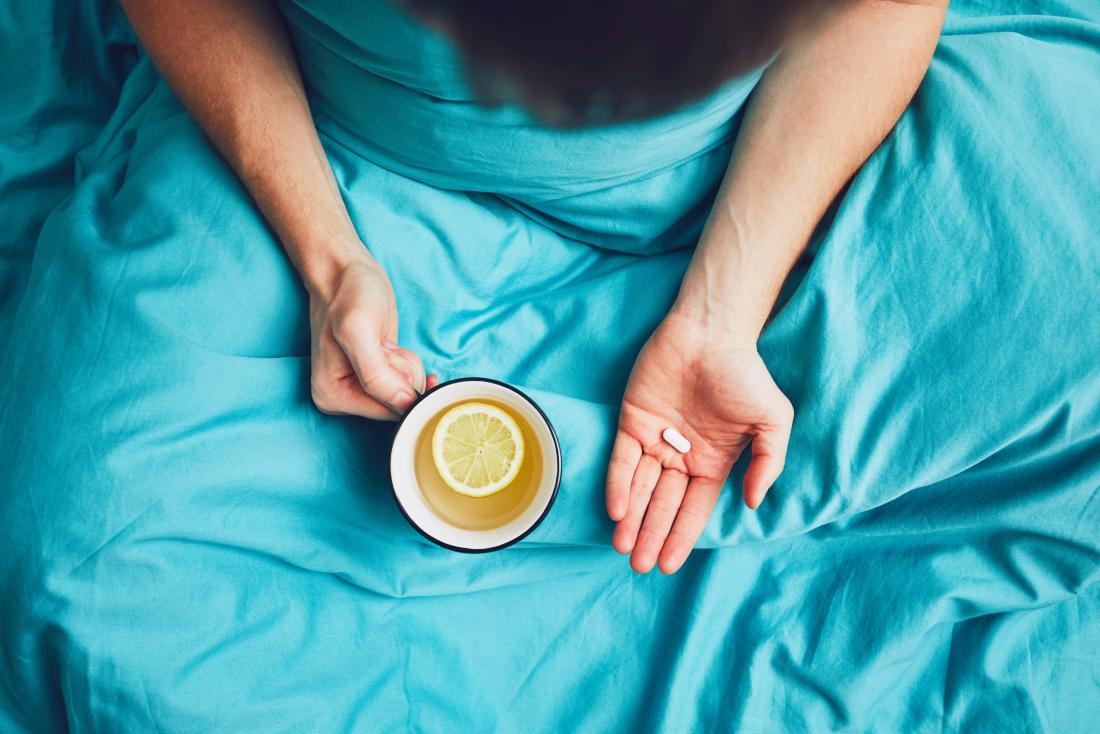 Top down view of person sitting under blue blanket holding mug of lemon tea and pill or supplement