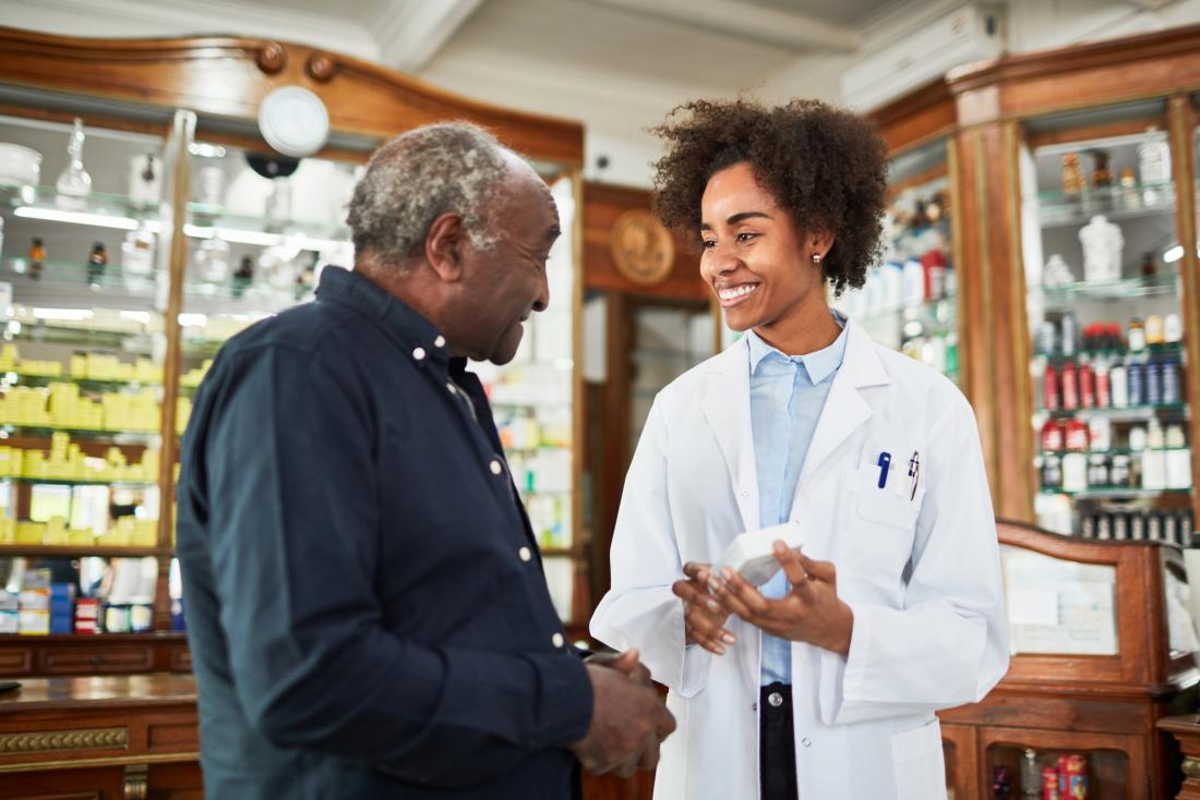 chemist assisting senior man, both smiling