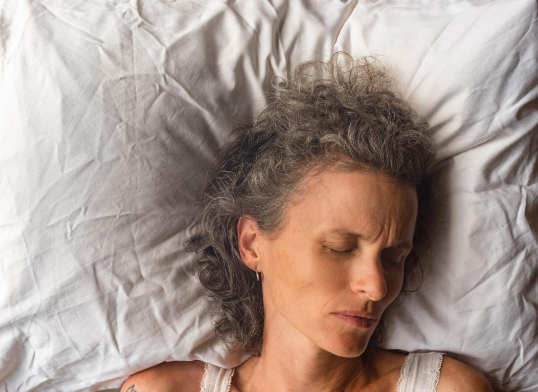close up of grey haired woman asleep on white pillow