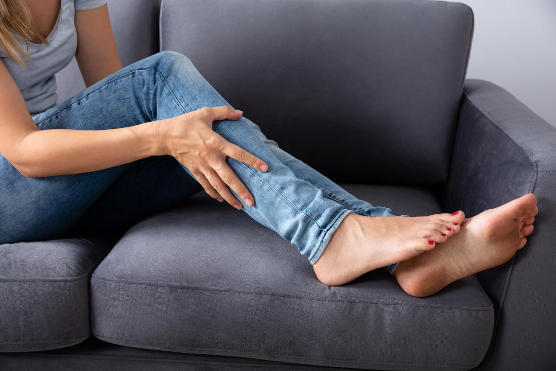 woman on sofa holding leg with muscle strain