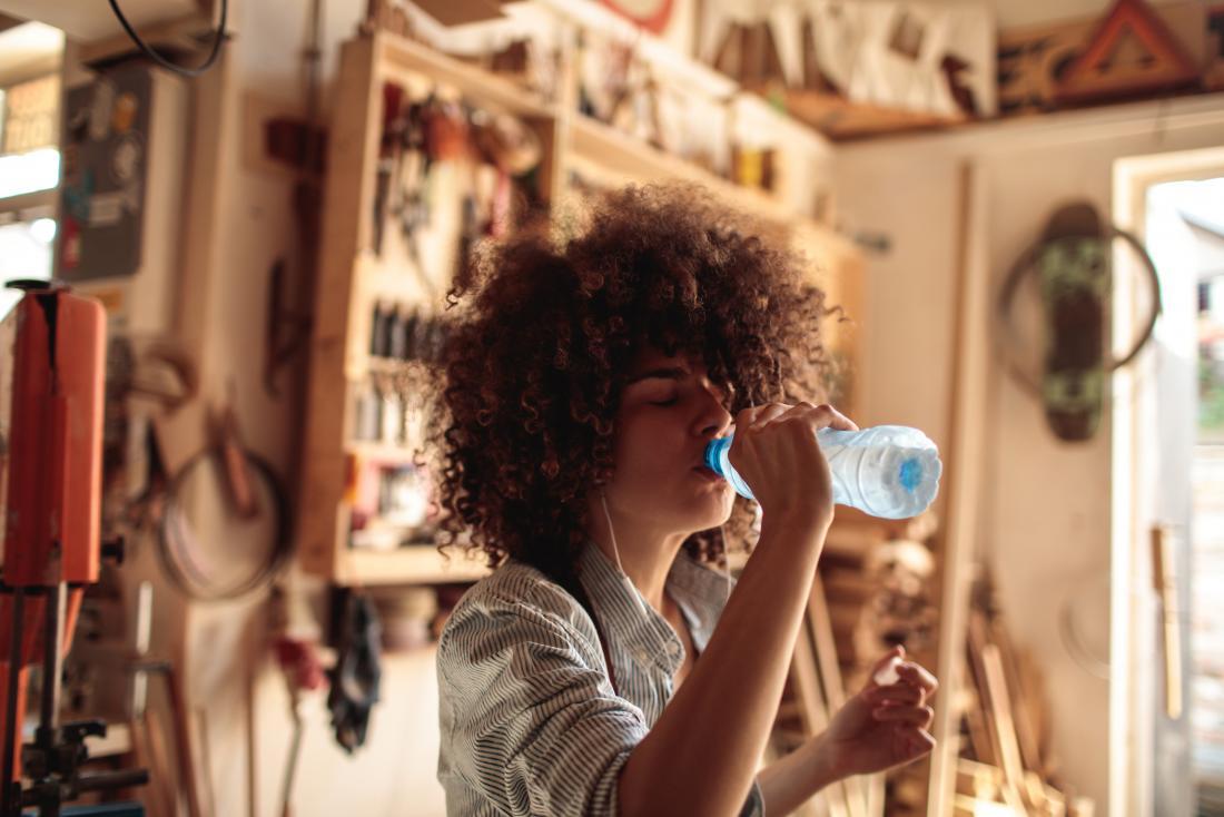 Una mujer que tiene sed después de consumir bicarbonato de sodio bebe una botella de agua en un taller de carpintería.