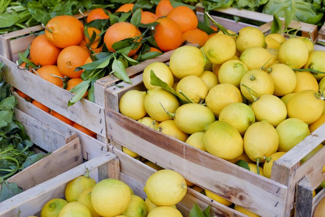 Cajones de madera que contienen limones y naranjas.