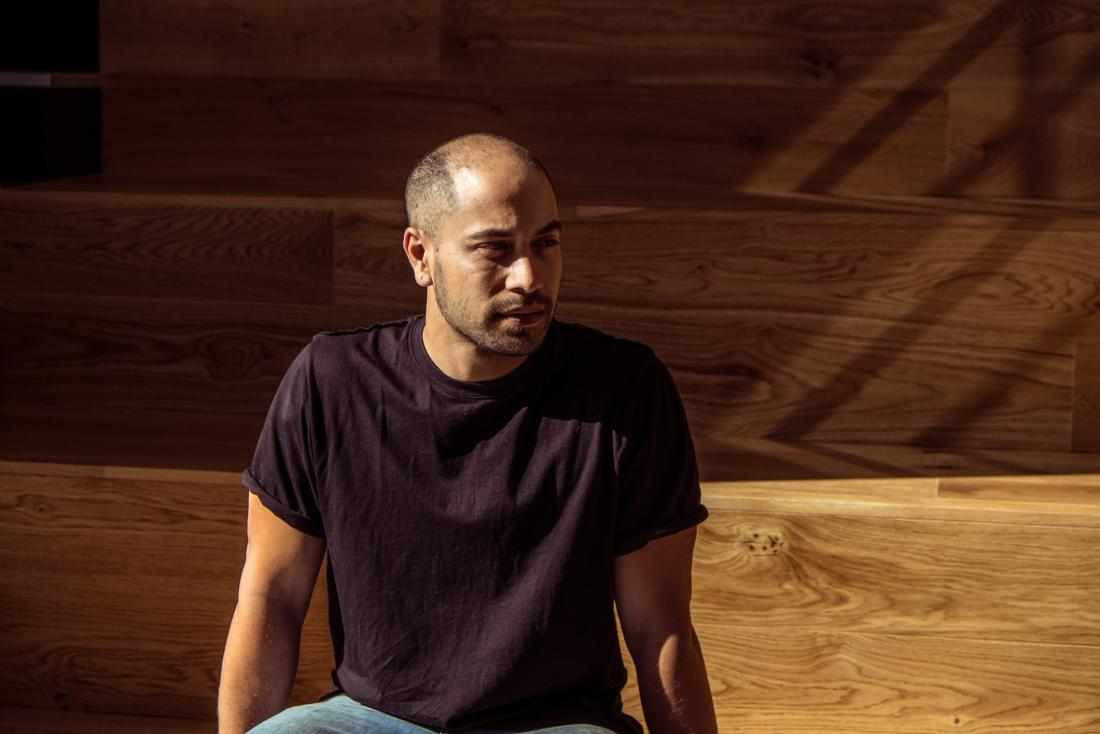 man in dark shirt in front of wooden background
