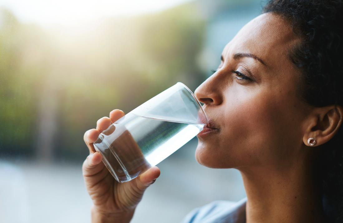 Woman drinking water due to dehydration which causes brown urine