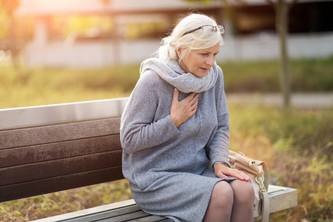 Woman with chest pain sitting on a bench