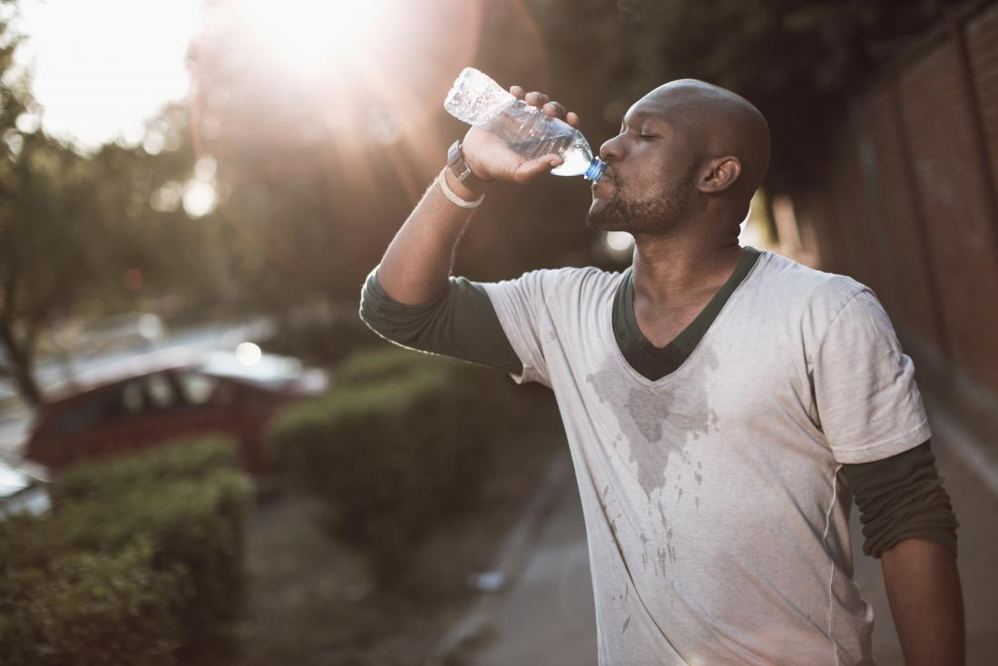 A man experiencing painful respiration and excessive sweating drinks from a water bottle outside.