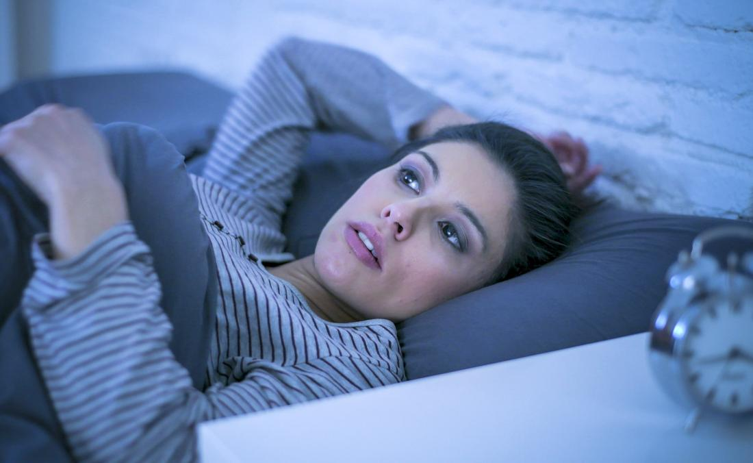 woman laying awake because of insomnia during early pregnancy