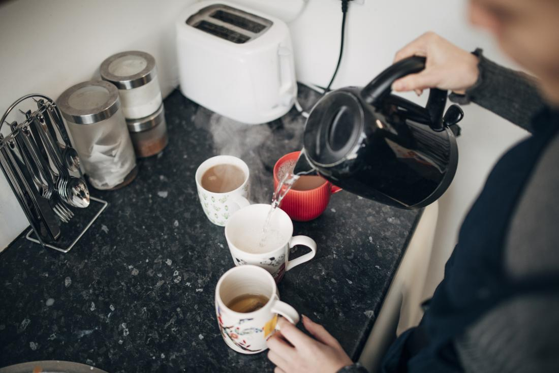 Person making coffee and tea hot drinks in a kitchen.