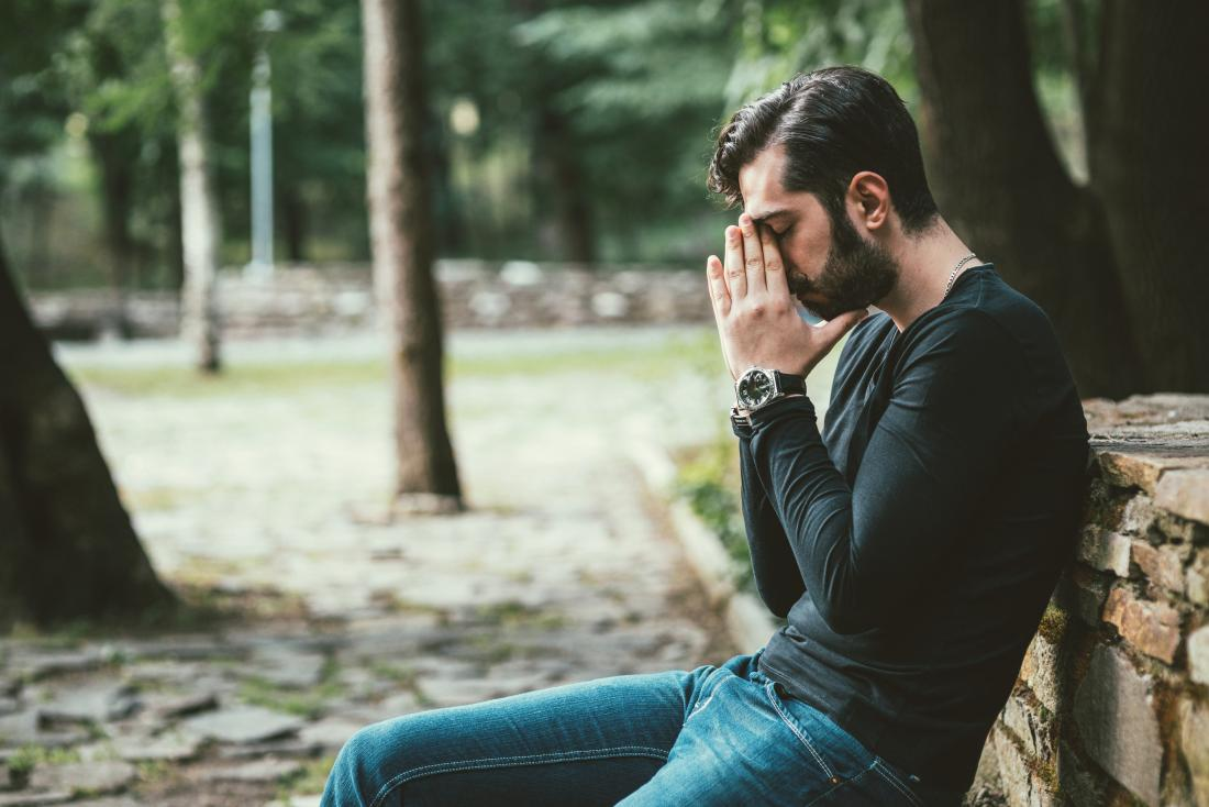 Stressed, depresses or anxious man sitting on park bench.