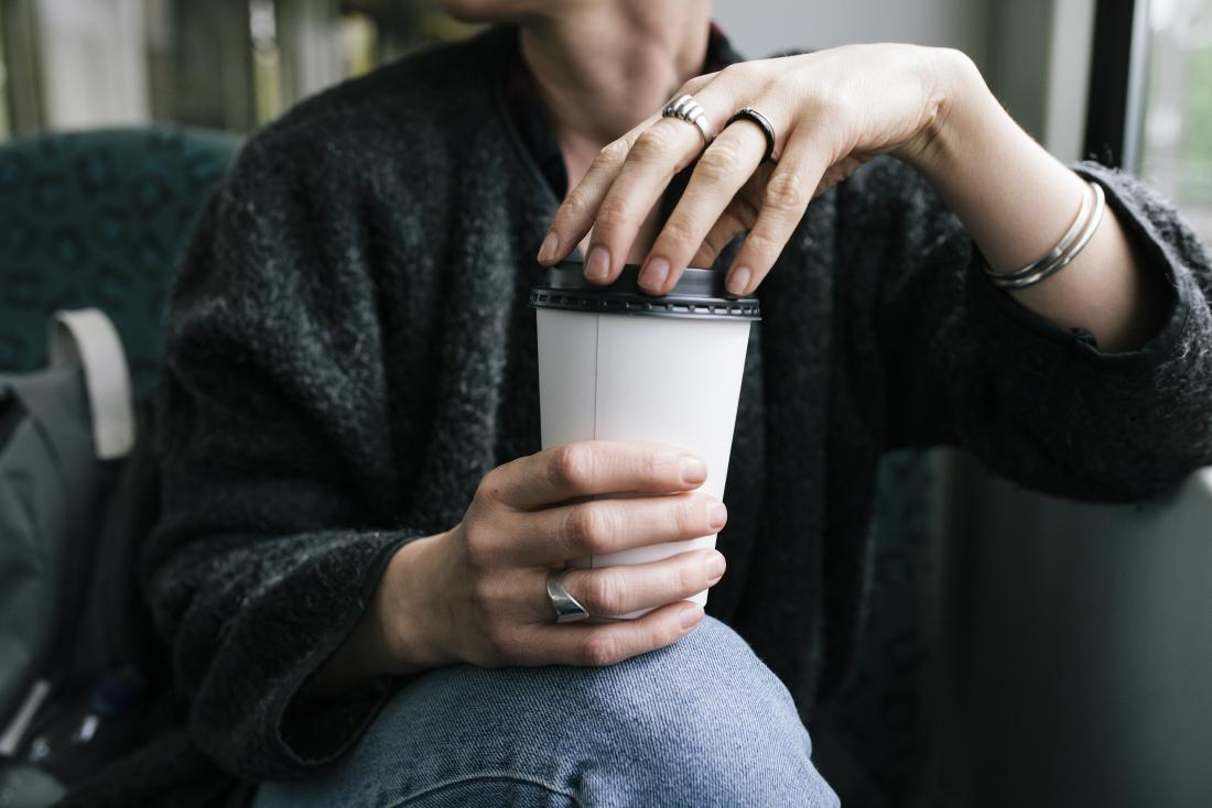 Woman experiencing caffeine withdrawal holding takeaway cup of coffee on public transport