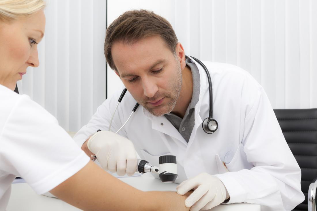 Dermatologist inspecting patients skin