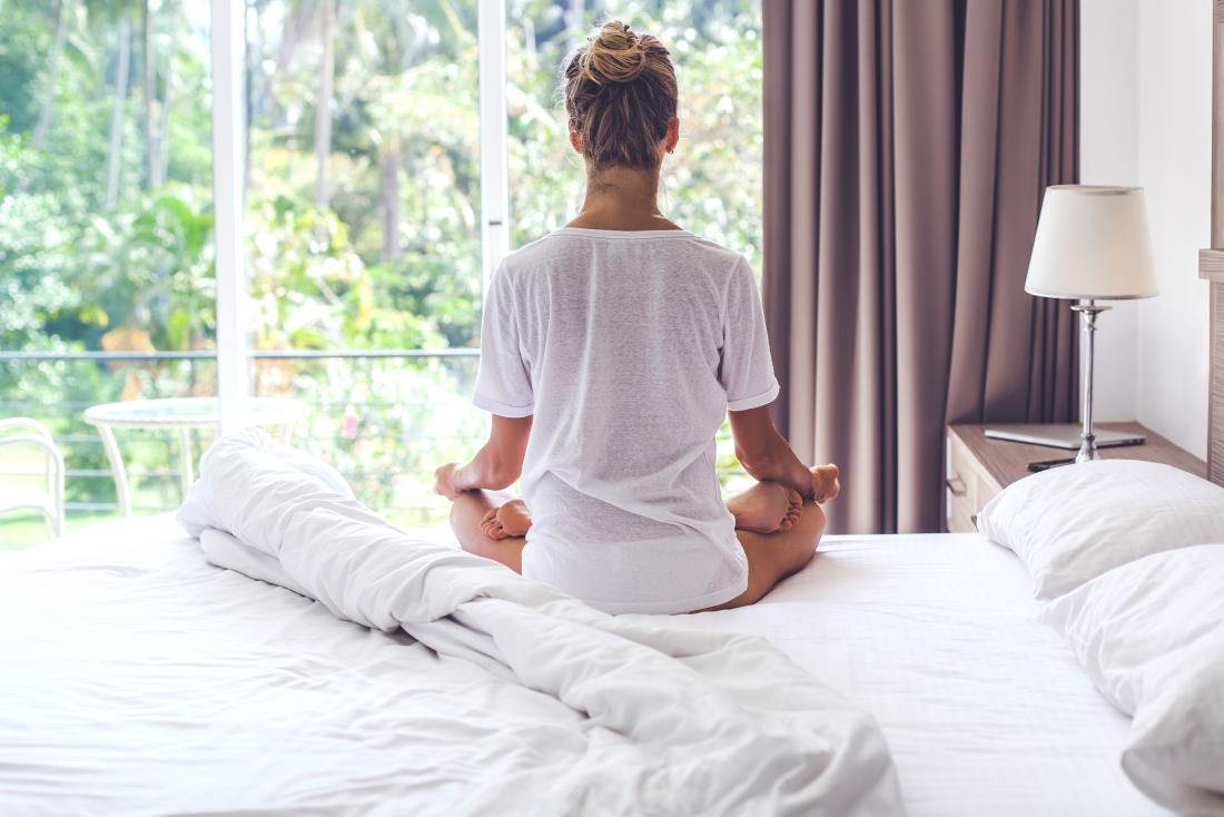 Woman sat on her bed meditating which may help with irregular periods