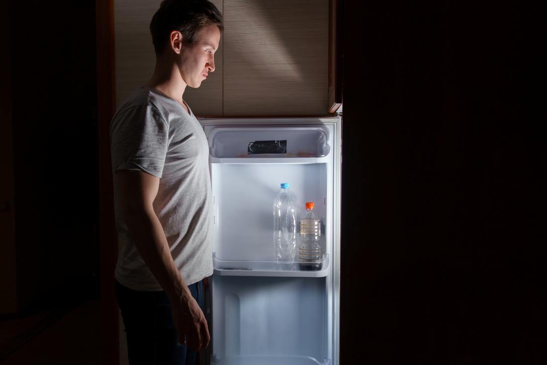 Man looking in a fridge at night