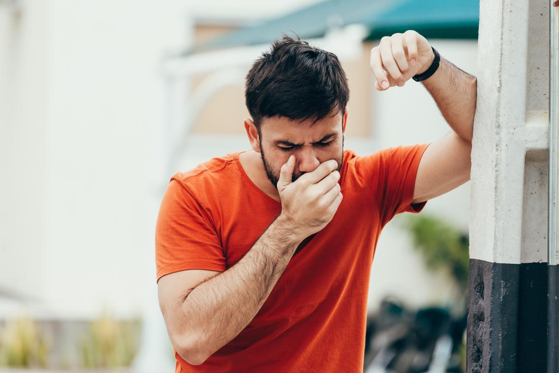 Man with nausea feeling sick holding hand over mouth