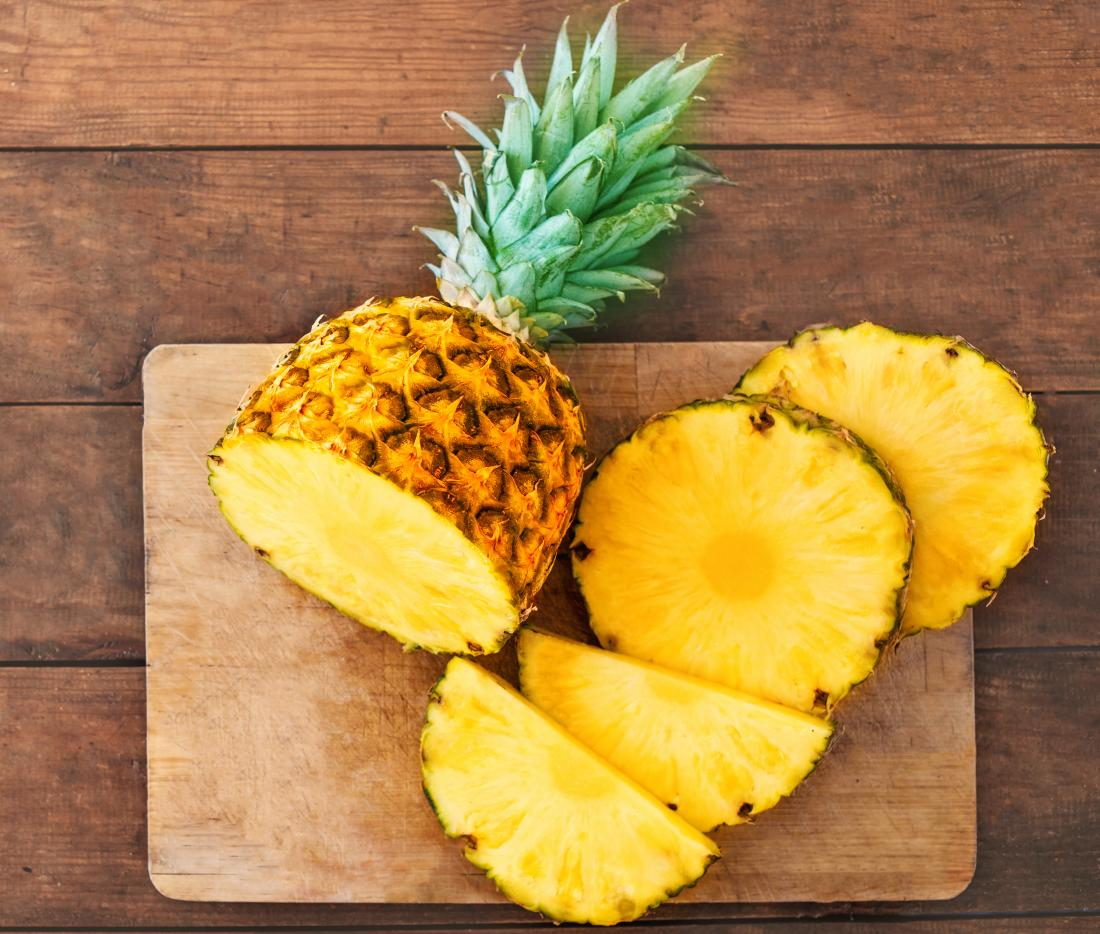 fresh pineapple sliced on chopping board