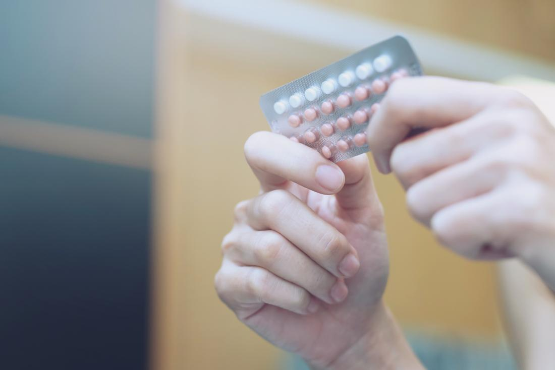 women holding packet of birth control pills to make period come faster