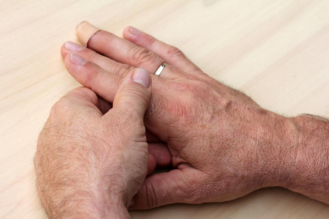 Person with finger pain holding hands due to injury