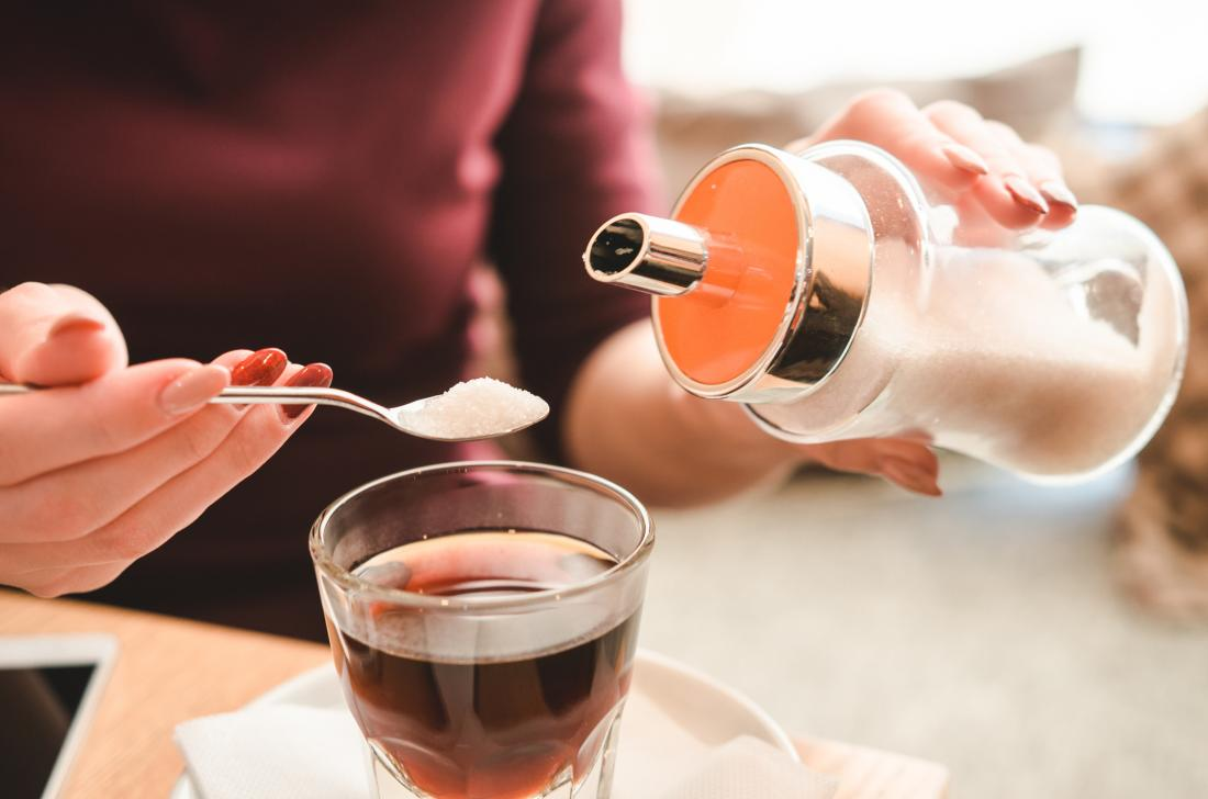 Woman pouring sugar into hot drink