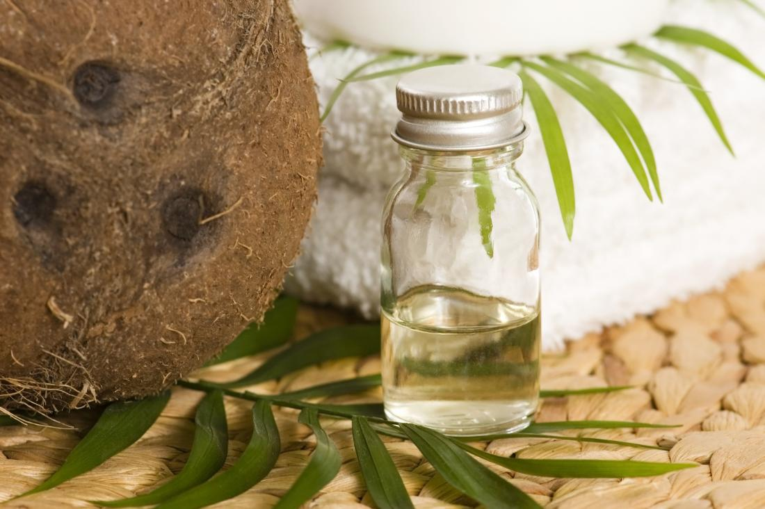Coconut oil in small glass jar next to towels and leaves.