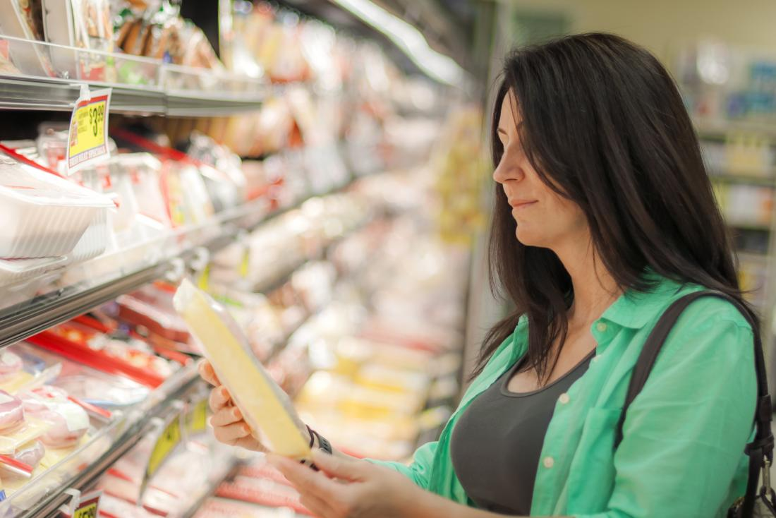 woman choosing frozen meat in meat aisle