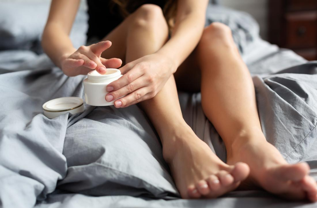 Person sitting on bed with bare feet applying lotion or cream to dry skin