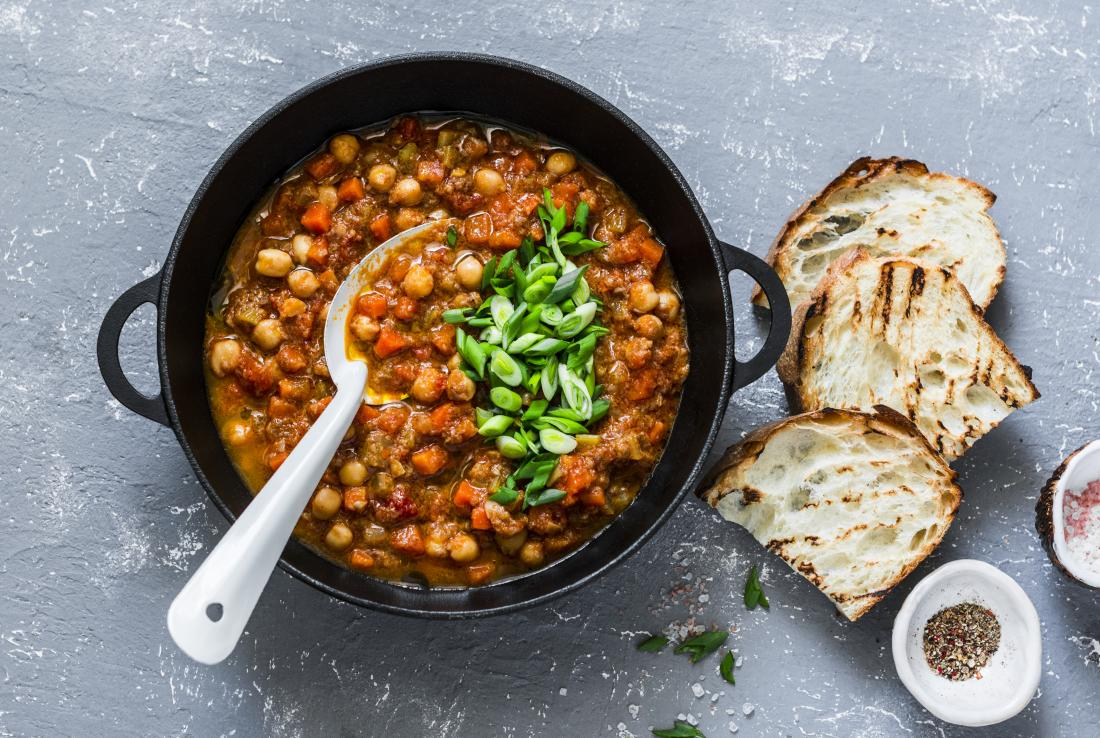 High-protein chickpea, vegetable and bean chili stew with bread and seasoning