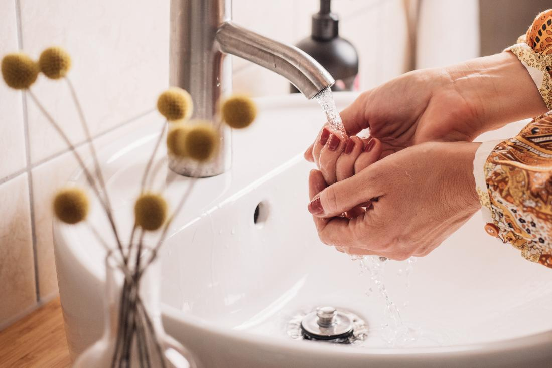 Woman washing her hands to stay healthy with a weak immune system