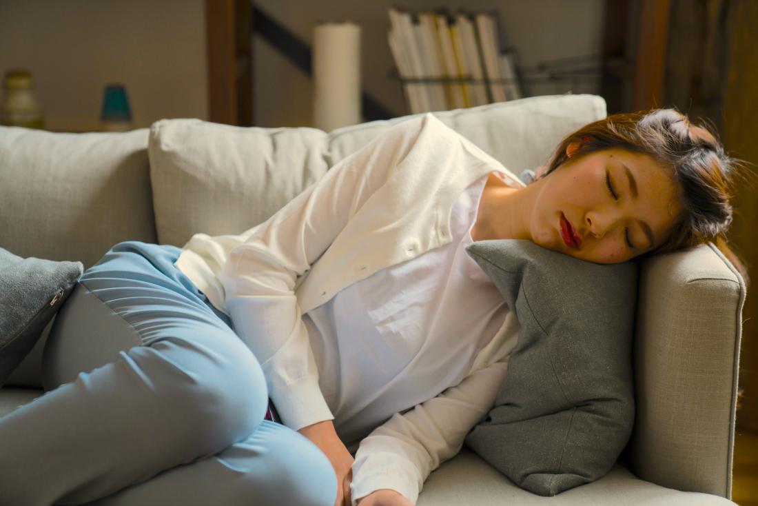 由于疲劳,女人睡着在沙发上,这是一个是ms症状