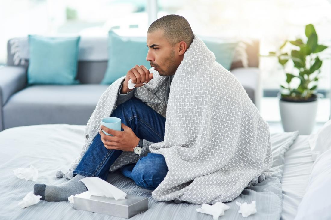MAn with flu sitting under blanket coughing and drinking tea because of asthma complications.