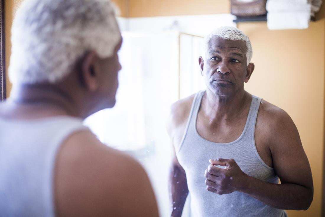 Mature senior man looking at face in mirror
