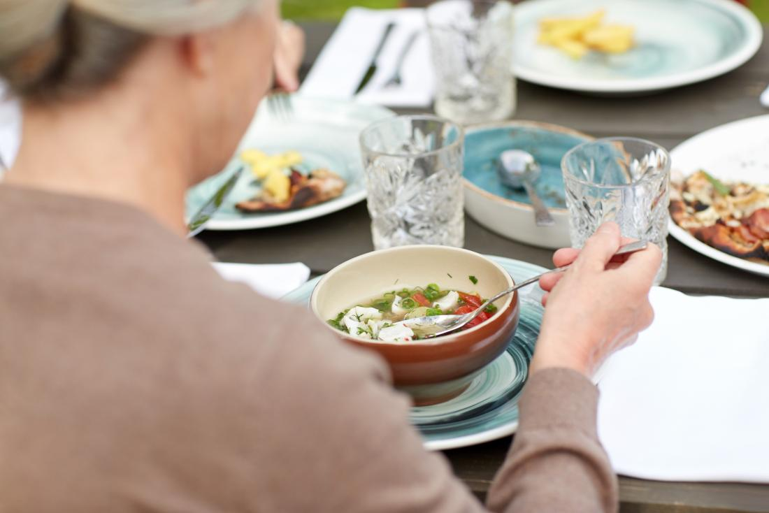 Woman eating small soup meal outdoors