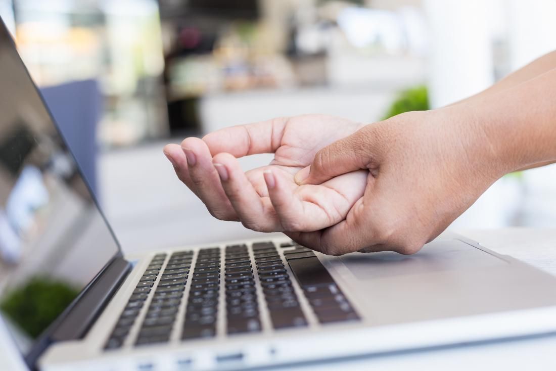 Person holding palm of hand in pain over laptop